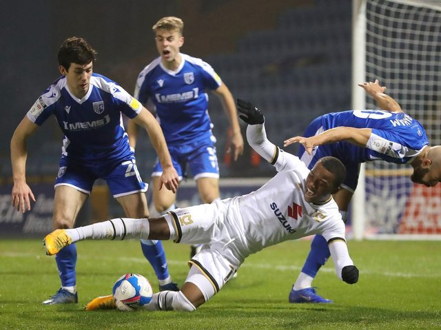 Ethan Laird is closed down by three Gillingham players