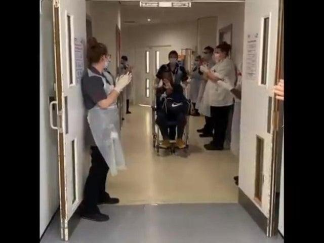 Nurses line the corridor to clap as a Covid patient leaves hospital