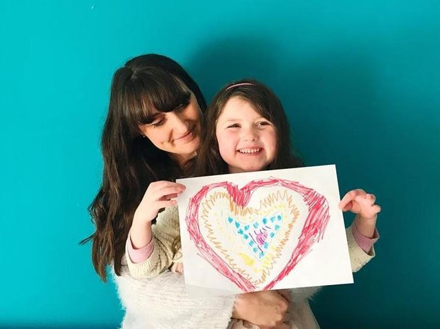 Lucy and her own daughter with a drawing about to be posted