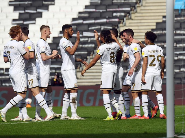 Dons celebrate with Will Grigg after he scored his fourth