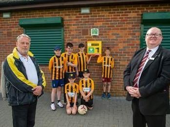Ian Lawson, chairman of Hanslope Hornets Football Club, and Alan Hames, sales manager for Davidsons Homes, with footballers from the club